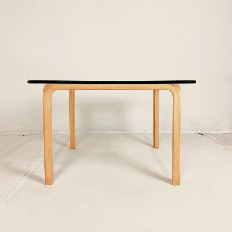 A pair of Classic Alvar Aalto design from 1946. These are from the 1970s. Four sections of birch steam bent to form the base with original glass top.