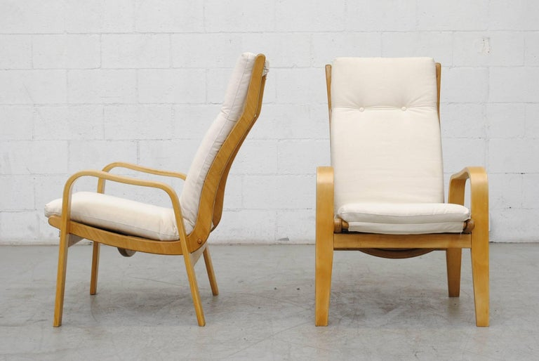 Pair of lounge chairs newly upholstered in natural canvas by Cees Braakman for Pastoe. Bent natural plywood frame in the style of Alvar Aalto. In good original condition with some signs of wear consistent with age and use.