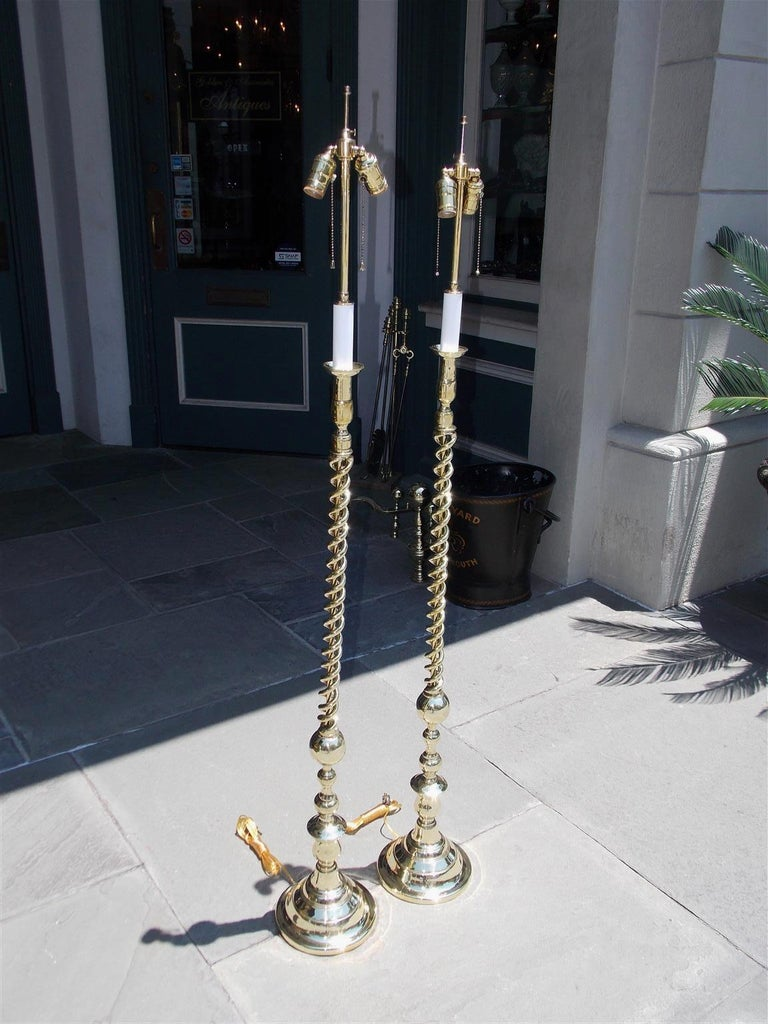 Pair of American brass spiral and bulbous form floor lamps resting on circular step back bases, Late 19th century. Pair were originally candle powered and have been electrified.