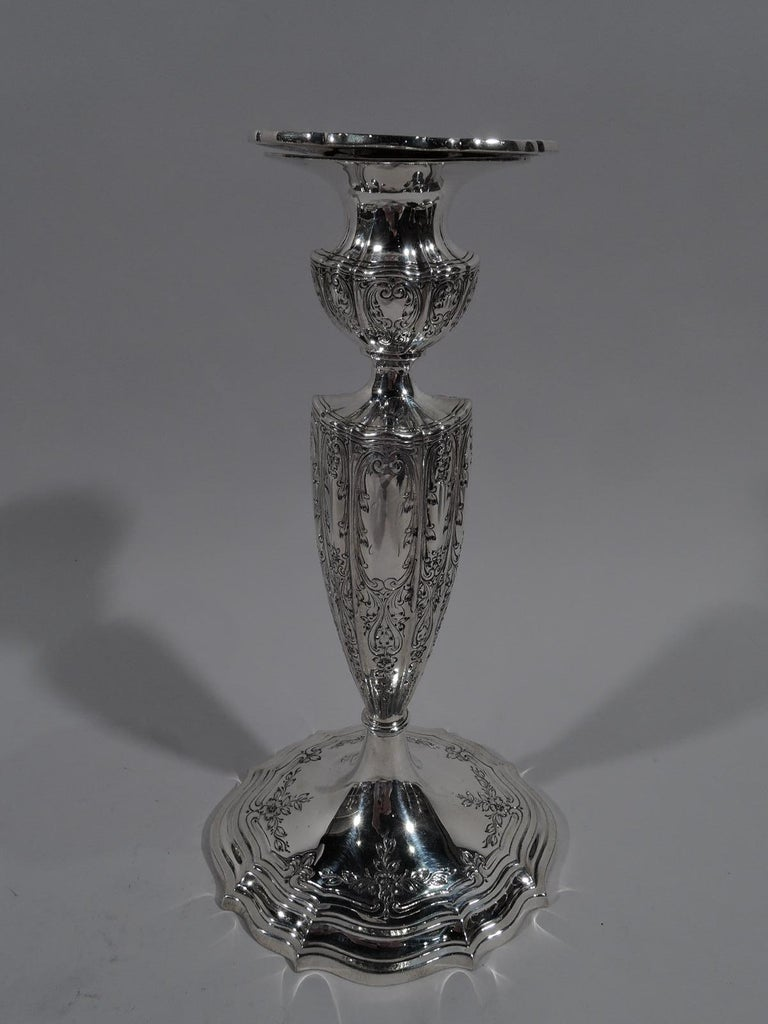 Pair of Edwardian Regency sterling silver candlesticks, circa 1910. Each: Ovoid with lobed shaft on raised and stepped foot; socket bellied with detachable bobeche. Bobeche and foot rim have scrolled rims. Engraved scrolling ornament with flowers