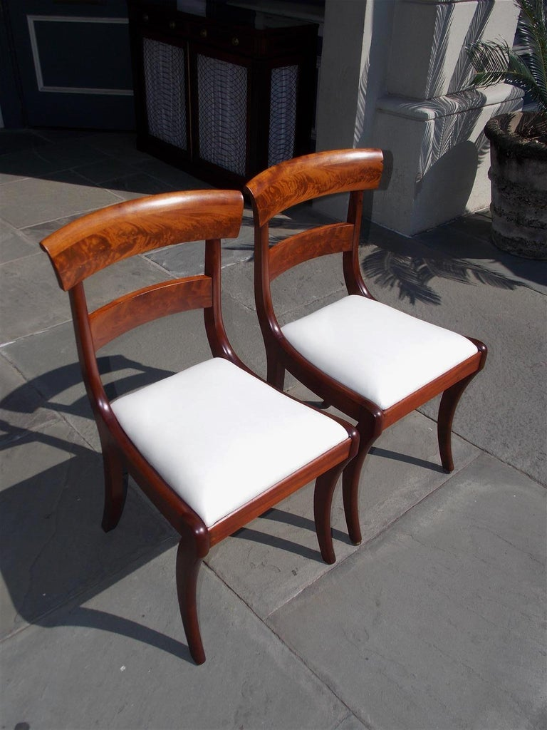 Pair of American Federal mahogany side chairs with carved splat backs, removable upholstered white muslin seats, and terminating on the original saber legs. Early 19th century.