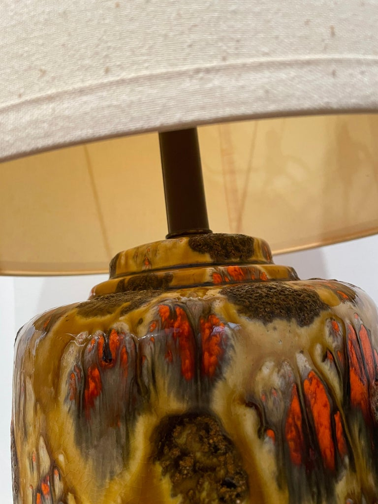 Beautiful pair of midcentury ceramic lava drip glazed table lamps. The pair includes original lampshades and together bring that MCM feel to your decor. Beautiful colors and glaze hard to find a matching set in this condition. And working.