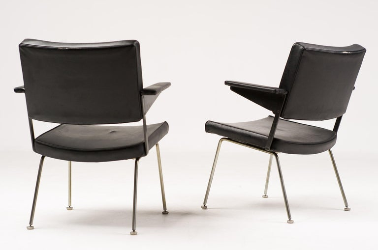 Nice pair of Gispen armchairs, designed by Andre Cordemeijer. Upholstered in the original black vinyl upholstery. The foam is still resilient, but the vinyl is cracked in front corners of the seat. Marked with label.