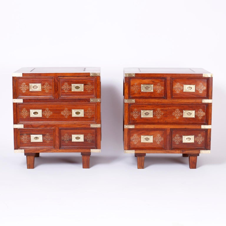 Pair of British colonial five-drawer stands crafted in indigenous rosewood with paneled sides and tops, brass campaign hardware, and featuring brass inlaid floral designs.