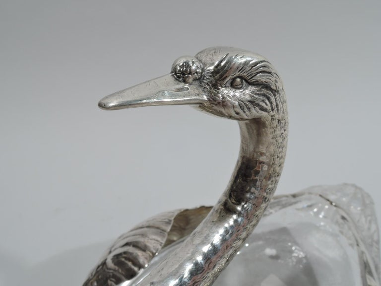 Pair of American Edwardian sterling silver and glass swans, ca 1920. Each: Glass body with imbricated tail feathers. Sterling silver mouth with plumy wings and graceful s-scroll neck and head with penetrating gaze and long and closed bill. Both
