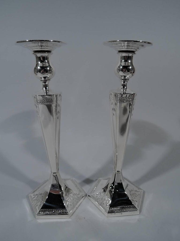 Pair of American Edwardian sterling silver candlesticks. Each: Tapering and faceted hexagonal shaft, raised hexagonal foot, and bulbous socket with wide and stepped detachable bobeches. Engraved stylized ornament: Leaves and flowers and imbricated