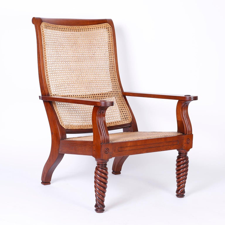 Refined pair of Anglo-Indian British Colonial plantation chairs handcrafted with mahogany featuring hand caned backs and seats, pegged construction, turned and twisted front legs and an overall elegant sophisticated form.