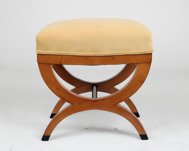 This beautiful pair of antique Biedermeier style stools are made out of maple wood and in good condition. The stools feature an X-design pedestal legs with a maple and ebonized color finish, and have been newly waxed and polished giving it a nice