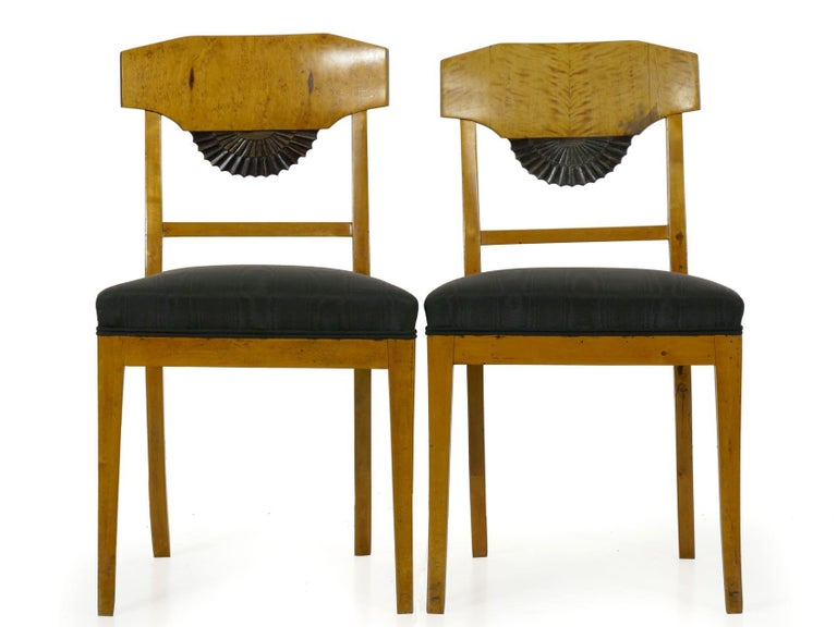 An incredibly attractive pair of Biedermeier style side chairs, they are crafted of birch with finely veneered crest rails of the same over fan-carved ebony stained embellishments in the splat. Probably from the last quarter of the 19th century, the