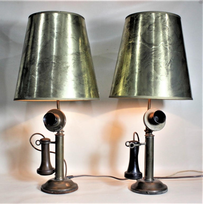 This very unique pair of table lamps began as a pair of brass and Bakelite candlestick telephones made by the Northern Electric Company of Canada in circa 1920. These authentic telephones have been wired and fitted with switches on their bases and