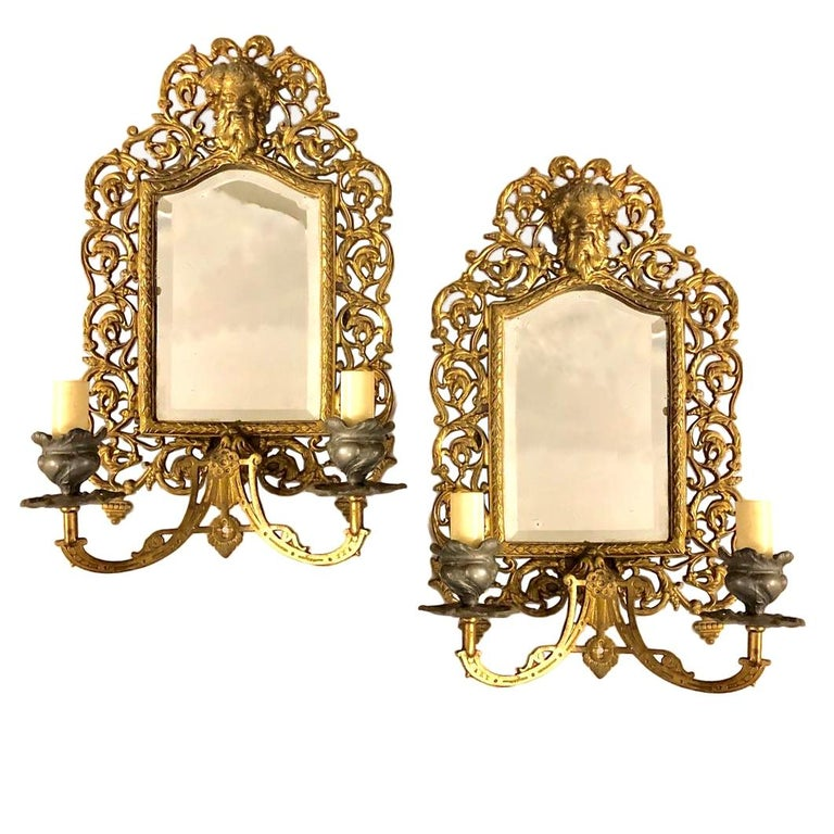Pair of French bronze sconces with mirror back, circa 1900. Scrolling foliage motif backplate and with Bacchus mask atop.