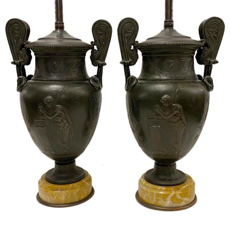 Pair of 19th century French bronze urns on marble bases, mounted as lamps.  Measurements: Height of body 12