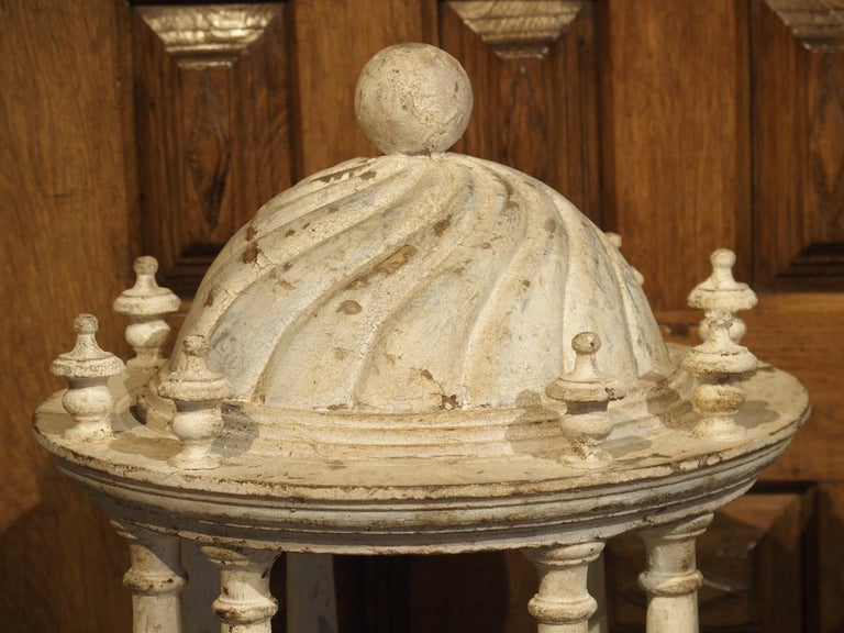 These parcel paint Italian colonnades are almost identical, except for their roof motifs and finials. One has a swirling design with a ball finial and the other has linear half rounds with a pine cone finial. Each has the same eight pillar