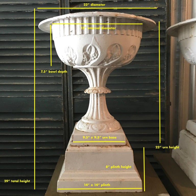 Pair of painted cast iron urns on square plinth bases by M. D. Jones & Co. of Portland Street, Boston, MA, circa 1904. These are the