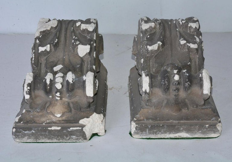The pair of antique cast corbels are hollow and are secured with iron horizontal bars. Can be hung for display or use as brackets for shelving. Also will work well for bookends.