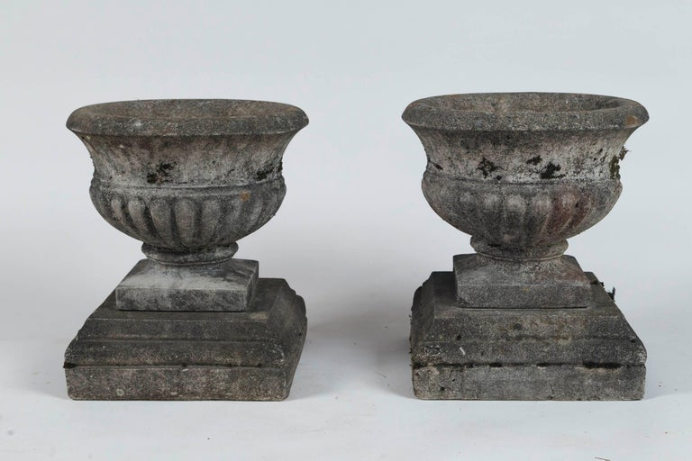 Pair of antique cast stone garden urns on bases, circa 1920. Tazza form urns with wonderful, weathered patina from a New England estate.