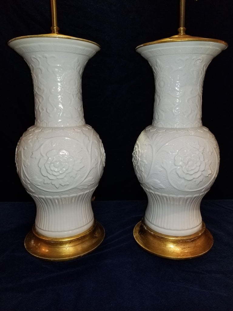 This is a fine pair of antique Chinese Blanc de Chine vases mounted as lamps. They are exceptionally handcrafted and glazed with exceptional craftsmanship throughout each. Found along the base of each vase and delicately hand-carved rose flowers