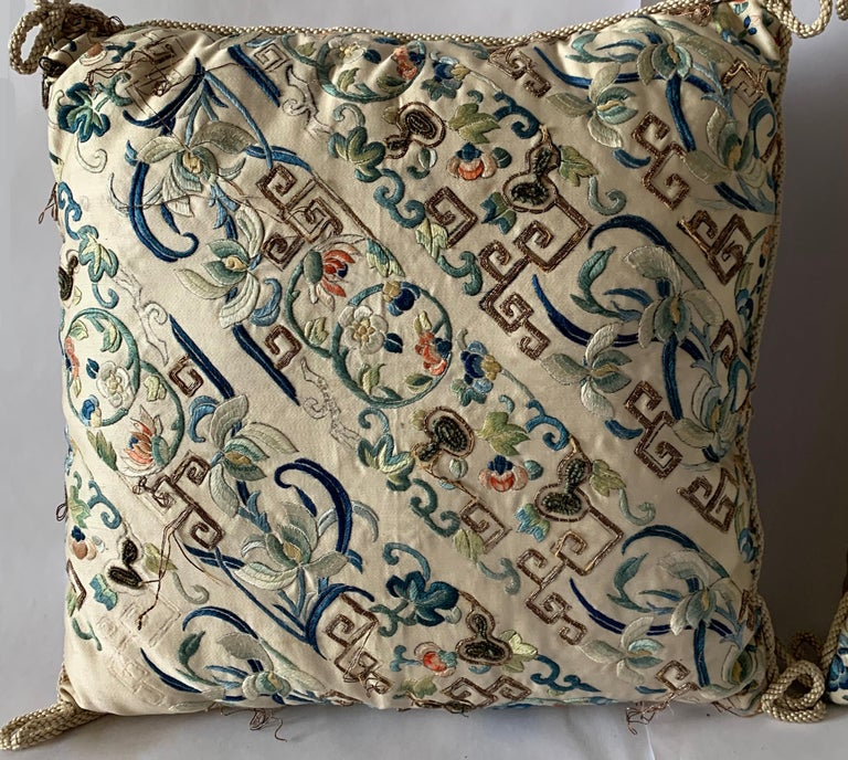 Pair of antique Chinese embroidered silk textiles made into custom pillows. Pale oyster grey silk with all over embroidery with gold couching (threading). Backed in coordinating silk fabric.