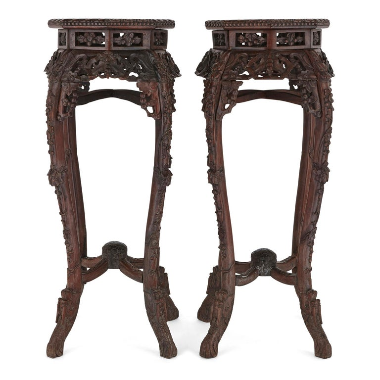 The stands in this matching pair are made from 'Hongmu' wood (Chinese hardwood). Each stand rests upon four stylised and flared dragon feet, which extend into four ornately carved cabriole legs. The legs are connected by upper and lower stretchers,