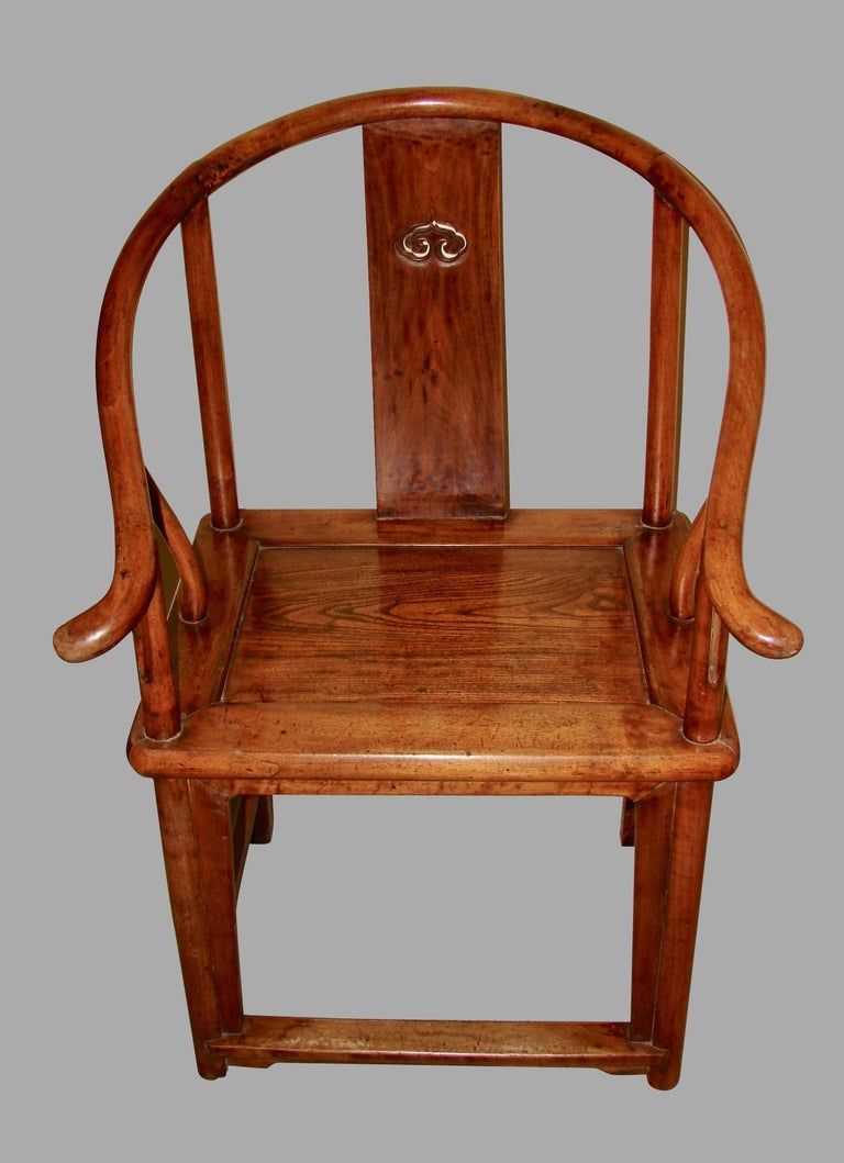 A pair of Chinese hardwood horseshoe back armchairs, each curved back with downswept arms and outswept hand grips, centring an elegant shaped pierced splat, flanked by cylindrical stiles continuing to undulating arm supports. The rectangular seat