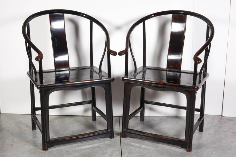 An unusually beautiful pair of antique Chinese horseshoe back chairs with striking lacquer finish. These gracefully shaped chairs will add a touch of elegance to any space. Dimensions: L 26, D 21 seat H 20, back H 39.5.