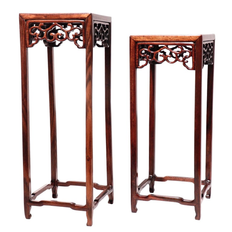 A set of two Chinese rosewood and burl wood curio display stands, in a tall pedestal form with thin legs and delicate pierced work apron in a ruyi vine design, elbowed cross stretchers near the base and center burl wood panel, varied in