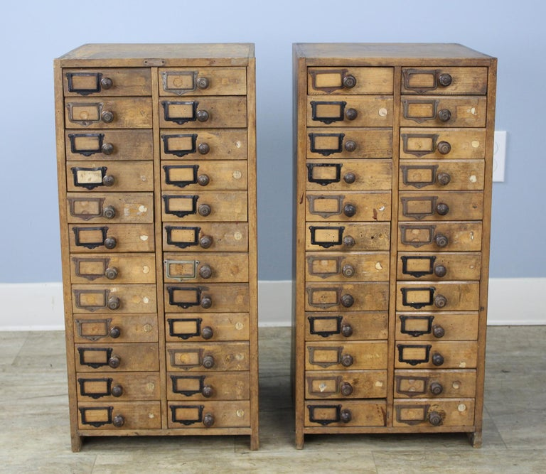 An interesting pair of French collector's drawers with original category labels. The knobs are wonderfully patinated from years of use. The variety of colored metal catalog card holders, along with the evenly distributed distress, has real visual