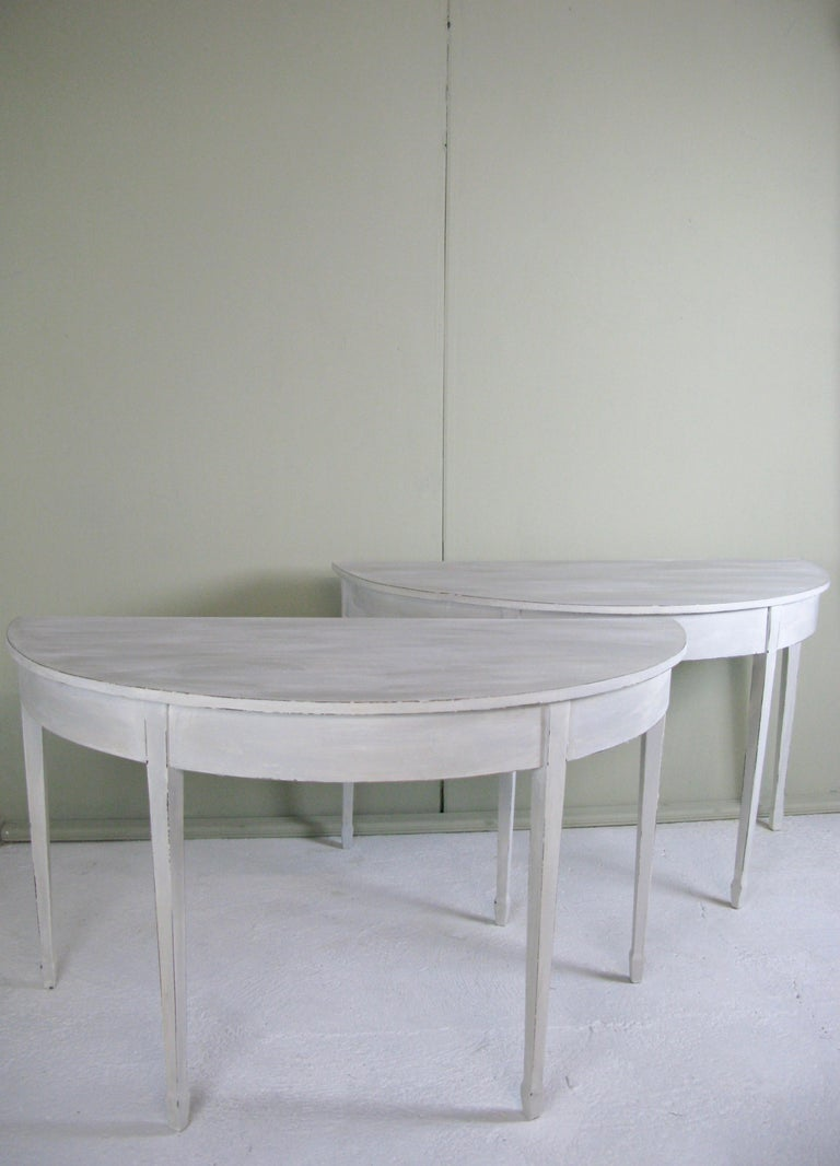 A lovely pair of decorative 19th century painted demi-lune tables painted in Gustavian style  Thes english tables from circa 1880s features a wide semi-circular top  This table is raised upon gently tapered legs.   Soft lovely patine with clear