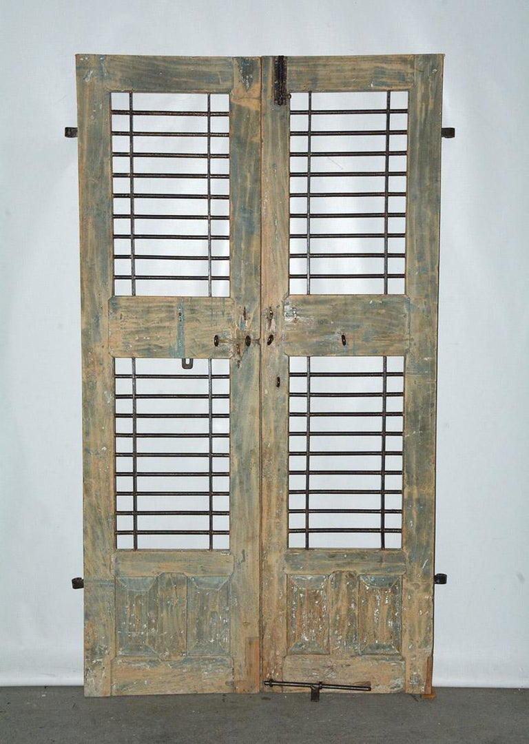 19th century Indian window or door shutters. Top and bottom are sets of original iron hardware for hanging the doors and latch for locking the shutters. Original painted finished cleaned and the remaining shows wonderful aged patina, full of