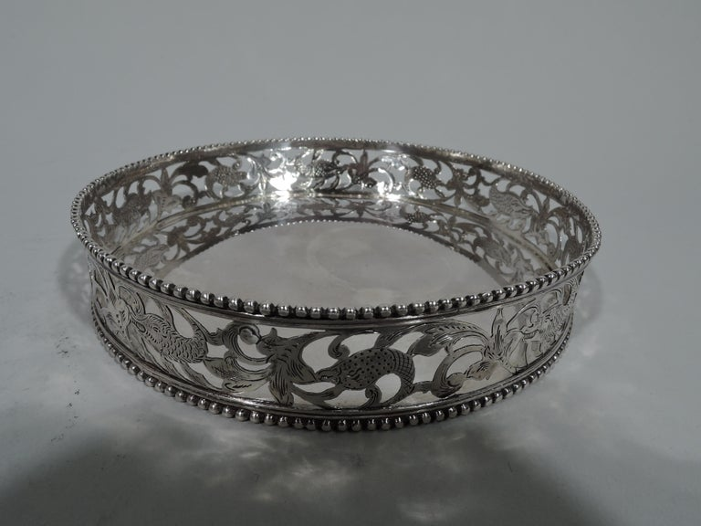 Pair of Dutch 833 silver wine bottle coasters. Each: Sides straight with pierced and engraved fantasy ornament: Flowers, leaves, and scaly piscine creatures. Beaded rims. Fully marked including date letters for 1890 and 1900. Total weight: 8.5 troy