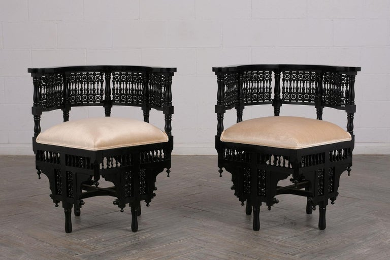 This pair of antique Syrian style corner chairs show amazing craftsmanship along the curved back and stretched legs. The pair features the original ebonized and patina finish and has newly upholstered seats covered in a pearl color velvet fabric
