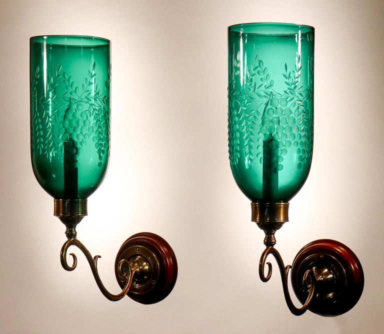 An exceptional pair of English hurricane shade sconces, circa 1890, with a deep green hue. These authentic hand blown glass shades have lovely straight form and are etched with a Classic grape motif. The wall sconces are newly electrified, with each