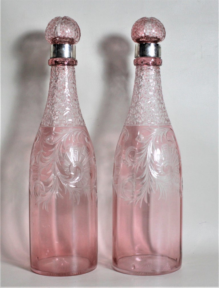 This pair of Victorian cut cranberry crystal bottle decanters were made in Sheffield England in circa 1895. These matching pink decanters have been ornately hand cut with swirled floral decoration on both sides and are done with a textured finish
