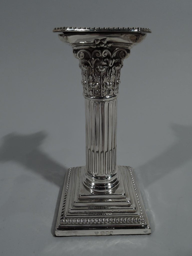 Pair of George V sterling silver candlesticks. Made by William Hutton & Sons, Ltd in London in 1910. Each classical column with stop-fluting, stepped and beaded square vase, and Corinthian capital. Bobéches concave and beaded. Underside felt lined.