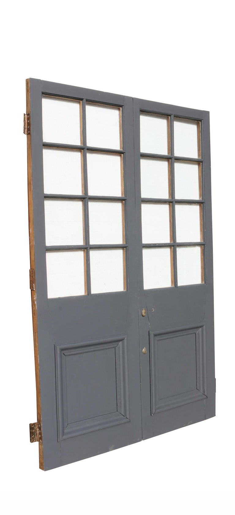 These doors have been painted on one side in a grey primer and feature single glazing. They are in good condition for their age, but do have four cracks to the glass.  Measures: Height 197.5 cm  Width 124.5 cm  Depth 5 cm  Weight 45 kg (for