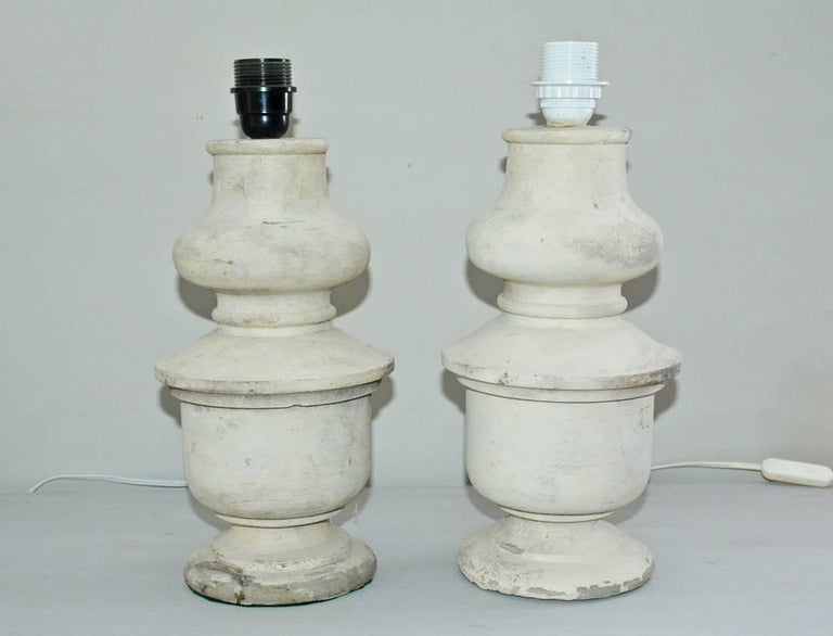 Great looking pair of shaped column form on round base. Made of cast stone with Belgium linen shades. Lamp sockets are two different colors but does not effect overall height of lamps. Sockets are for euro shades. We can rewire if you would like to