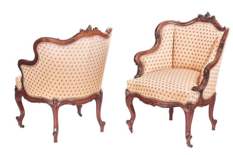 Fine pair of antique French carved walnut library chairs having outstanding shaped carved tops and arms with a shaped carved frieze. They are raised on beautifully designed and expertly carved cabriole legs on original castors. They upholstered in a