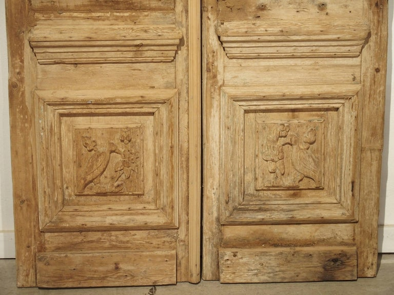 These antique doors are made of carved pine, and were salvaged from a property in Egypt, likely close to Cairo. The lower panels show unique carvings of birds, while the upper sections are more architectural in nature.  In the 19th century, France
