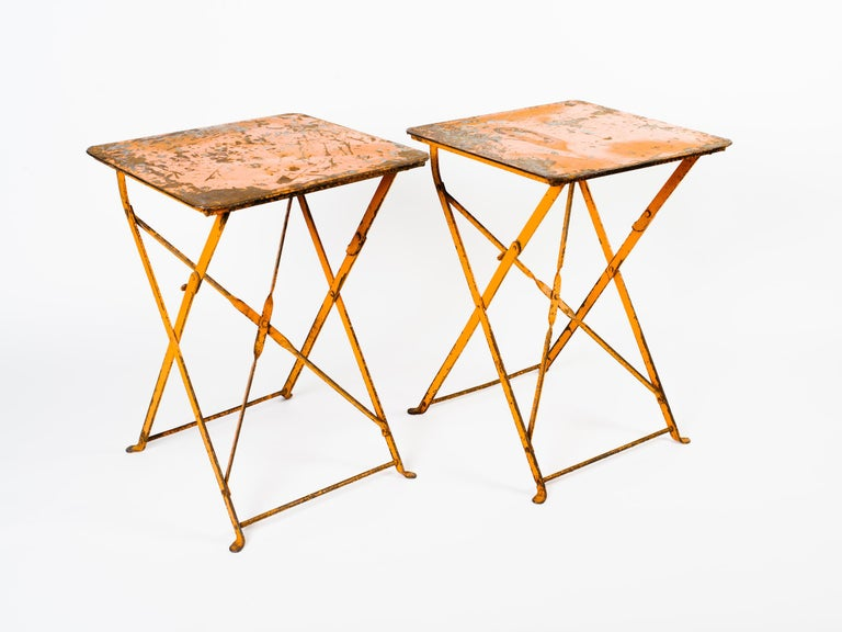 Pair of 1930s industrial French folding iron bistro tables with beautiful patina on the metal and original orange paint. Exhibits wear on the paint throughout, adding to their rustic charm and beauty. Can be used indoors as side tables or outdoors