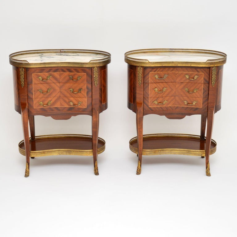 Pair of antique French style marble-top kidney shaped side tables with three drawers in each. They have pierced gilt metal galleries with swags around the marble tops and lower tiers. They also have gilt bronze mounts, feet and handles. The wood is
