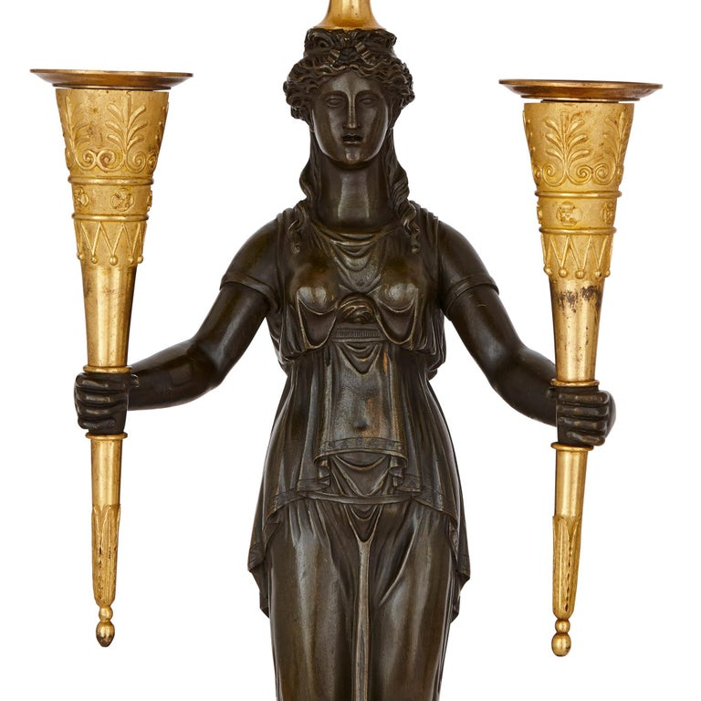 These bronze candelabra were created in France in circa 1810, when Napoleon Bonaparte was Emperor. The candelabra combine neoclassical and ancient Egyptian motifs, in a manner characteristic of Empire period decorative art.   The candelabra have