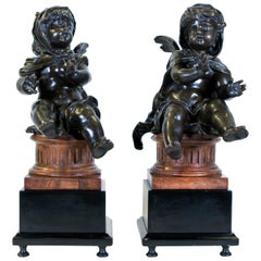 Pair of Antique French Patinated Bronze Winged Putti Seated on Fluted Plinths