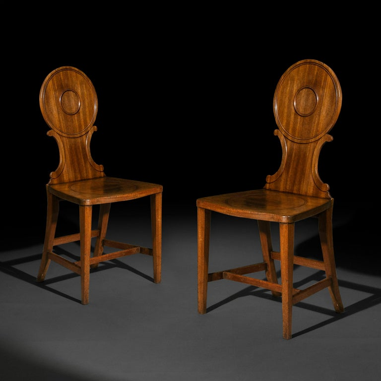 A fine pair of mahogany hall chairs of the Chippendale period, 