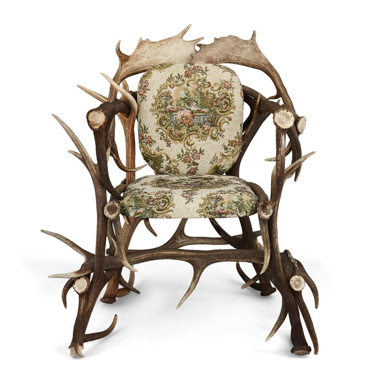 Pair of antique German Antler chairs with rococo style upholstery.