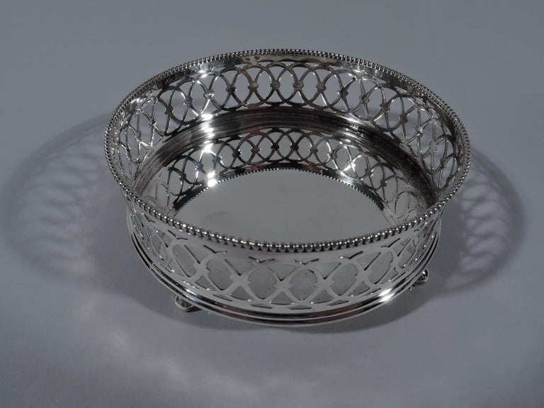 Pair of Edwardian sterling silver wine bottle coasters. Made by Gorham in Providence in 1896. Each: Round with gallery sides comprising pierced interlaced circles, and beaded rim. Four leaf-mounted volute supports. Fully marked including date symbol