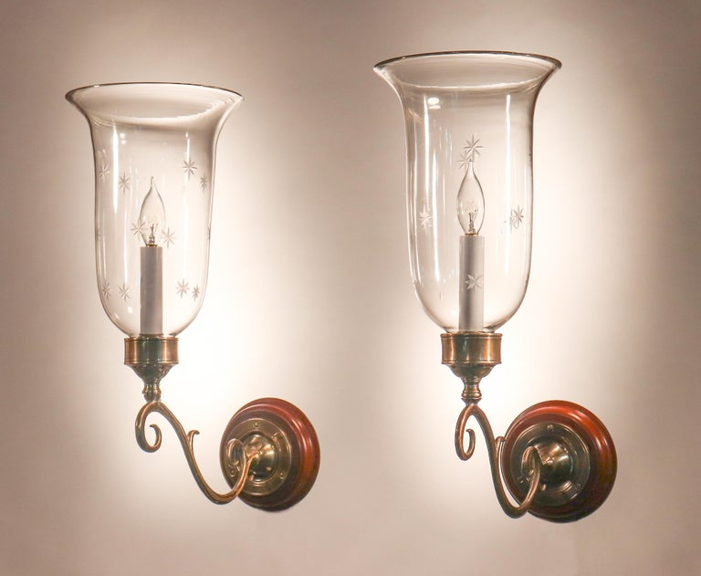 A lovely pair of flared hurricane shade wall sconces from England, circa 1900. These graceful shades have a finely etched star motif, as well as desirable air bubbles in the hand blown glass that speak to the quality and age of the shades. The