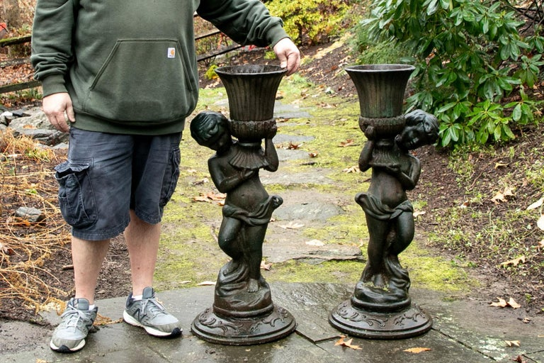Pair of antique iron Caryatid garden figures, two classical style youths wearing drapery around their waists support fluted footed urns held up in their arms. The circular cast bases with leafy scrolled decoration. 