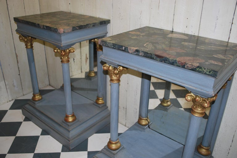 A rare and unusual pair of Italian console tables in the classical taste, with lovely granite tops. Standing on plinth bases with carved Corinthian capitals and tapered columns.  The backs are framed  mirrors. Painted in a later grey blue with