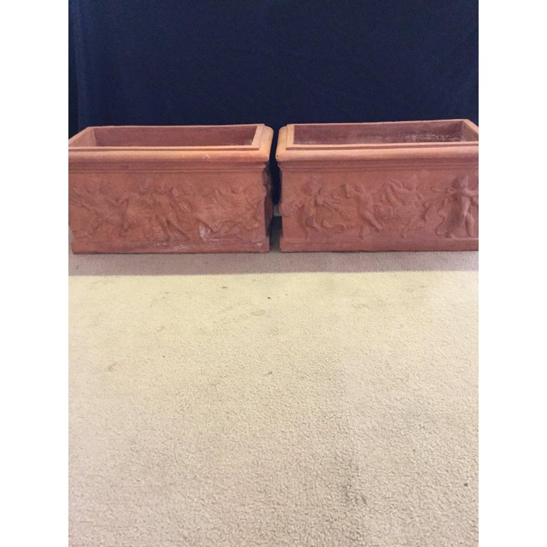 Beautiful pair of antique Italian terracotta garden planters with cherubs. All four sides of this pair of garden planters have different motifs and date to the 1920s. This lovely pair of antique Italian terracotta planters have dimensions as
