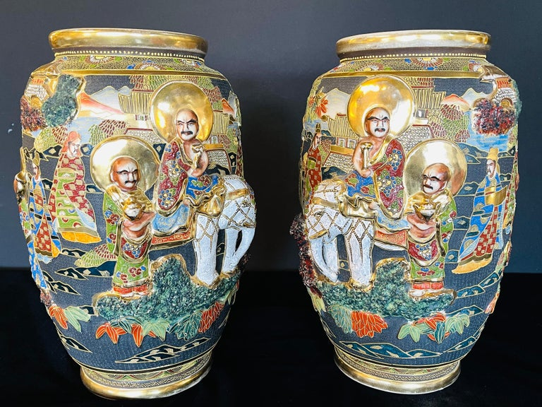 Pair of antique Japanese Satsuma vases. Each with opposing Scenes of figures and raised elephants. The pair in good condition.
